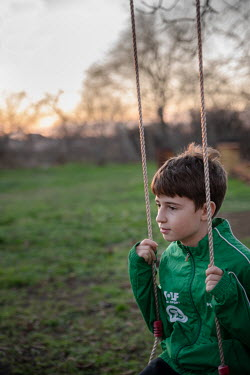 Galya Ivanova Boy in green jacket sitting on swing