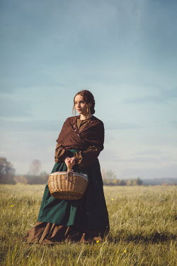 Joanna Czogala Young in Victorian dress holding basket in field