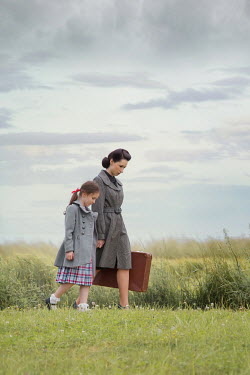Joanna Czogala Mother and daughter walking with suitcase in field