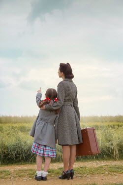 Joanna Czogala Mother and daughter with suitcase in field