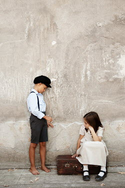Kerstin Marinov Children with suitcase by concrete wall