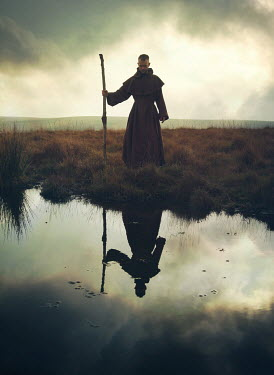 Mark Owen Monk with stick by pond in field