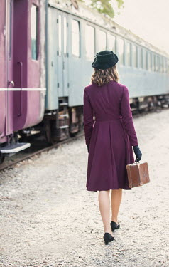 Nikaa Young woman in 1940s dress with suitcase at train station