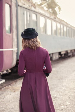 Nikaa Young woman in 1940s dress at train station