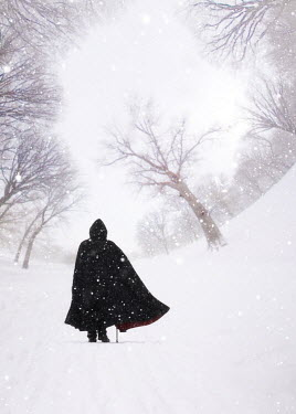 ILINA SIMEONOVA Man in cloak walking on warped park path in snow