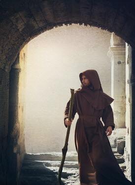 Mark Owen Monk with stick under archway