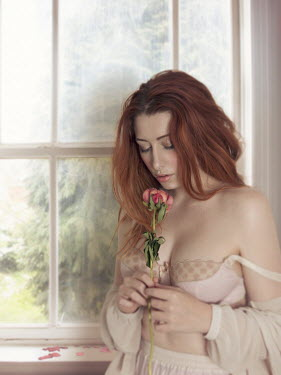 Victoria Davies Young woman with flower by window