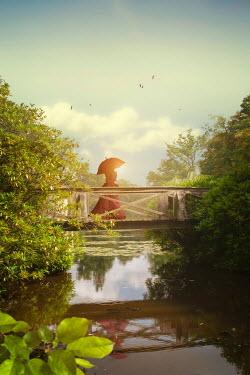 Victoria Davies Woman in Victorian dress with umbrella walking on bridge over river