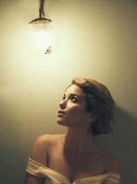 Eve North Young woman under light bulb with moth