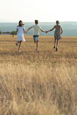 Galya Ivanova Children holding hands and running in field