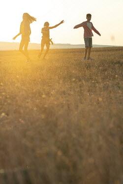 Galya Ivanova Children dancing in field at sunset