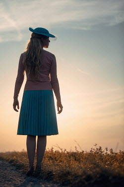 Magdalena Russocka retro woman standing in field at sunset