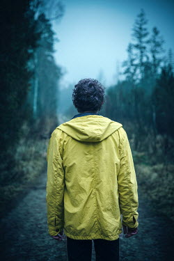 Natasza Fiedotjew Young man in yellow raincoat standing in woods
