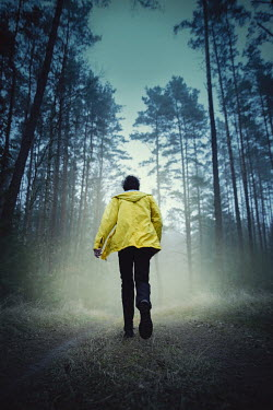 Natasza Fiedotjew Young man in yellow raincoat running in woods