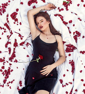 Eve North WOMAN LYING ON BED WITH ROSE PETALS Women