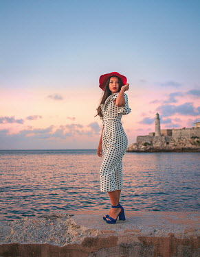 Eve North GIRL IN DRESS AND HAT BY SEA AT SUNSET Women