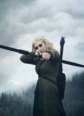 Mark Owen WOMAN POINTING BOW AND ARROW IN COUNTRYSIDE Women