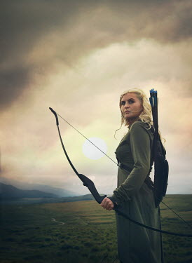 Mark Owen WOMAN WITH BOW AND ARROW IN COUNTRYSIDE AT DUSK Women