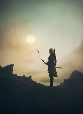 Mark Owen WOMAN WITH BOW AND ARROW IN COUNTRYSIDE AT SUNSET Women