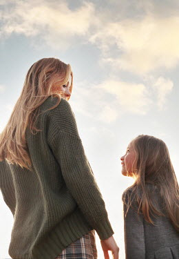 Buffy Cooper HAPPY MOTHER AND DAUGHTER OUTDOORS WITH BLUE SKY Children