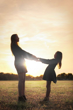 Buffy Cooper MOTHER AND DAUGHTER HOLDING HANDS IN SUNLIT FIELD Children