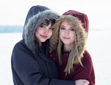 Elisabeth Ansley TWO WOMEN WITH FUR HOODS HUGGING OUTDOORS IN SNOW Women