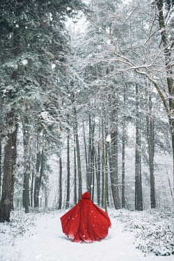 Jovana Rikalo WOMAN WITH RED CAPE IN SNOWY FOREST Women
