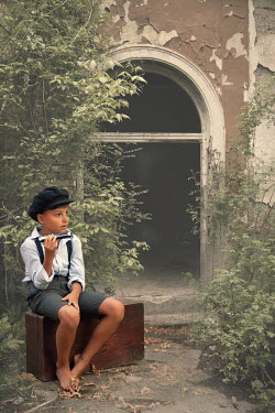 Kerstin Marinov BOY WITH HARMONICA SITTING ON SUITCASE OUTSIDE CRUMBLING HOUSE Children