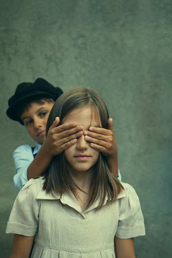Kerstin Marinov LITTLE BOY COVERING EYES OF YOUNG GIRL Children