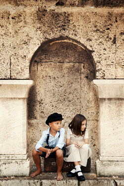 Kerstin Marinov LITTLE GIRL AND BOY SITTING IN STONE ALCOVE OUTDOORS Children