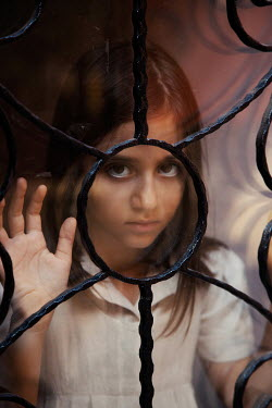 Kerstin Marinov LITTLE GIRL STARING FROM BEHIND WROUGHT IRON WINDOW Children