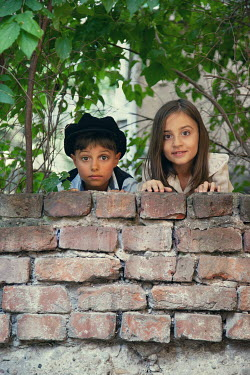 Kerstin Marinov GIRL AND BOY WATCHING FROM BEHIND GARDEN WALL Children