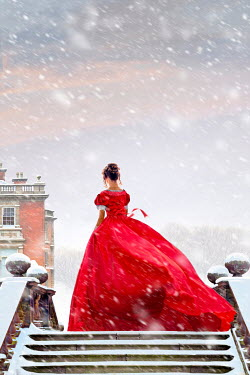 Lee Avison Victorian woman in a red dress in a winter snow storm