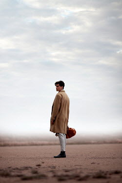 Miguel Sobreira Man in Coat Carrying Holdall Walking on Sandy Plain