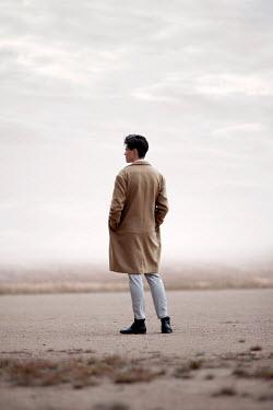 Miguel Sobreira MAN WITH COAT STANDING IN DESERT Men