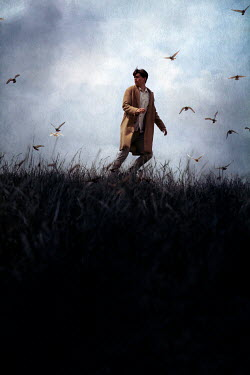 Miguel Sobreira MAN IN COAT RUNNING IN FIELD WITH BIRDS Men
