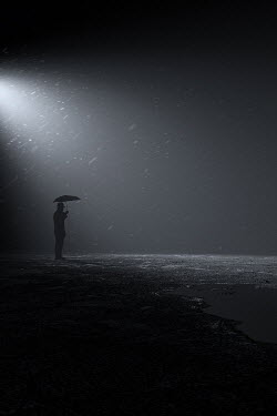Andrei Cosma SILHOUETTED MAN WITH UMBRELLA IN RAIN AT NIGHT Men