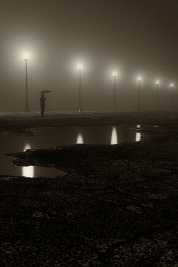Andrei Cosma SILHOUETTED MAN WITH UMBRELLA BY LAMPPOSTS AT NIGHT Men