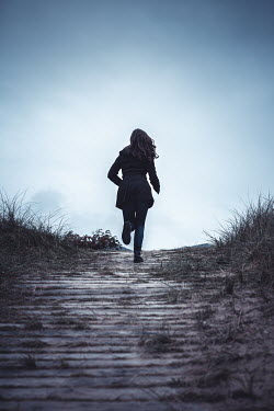 Marie Carr GIRL RUNNING ON SANDY PATHWAY AT DUSK Women
