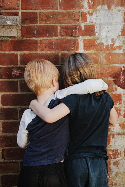 Matilda Delves LITTLE BOY AND GIRL HUGGING BY WALL OUTDOORS Children