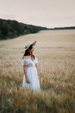Angela Ward-Brown Woman in straw hat and white dress in field Women