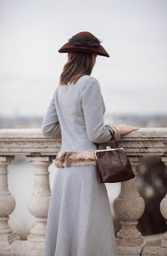 Nikaa Young woman in 1920s hat and coat standing by balustrade