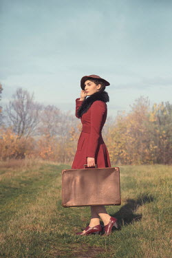 Joanna Czogala Young woman in red coat with suitcase in field