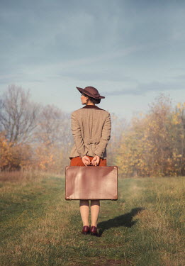 Joanna Czogala Young woman with beige coat and suitcase standing in field