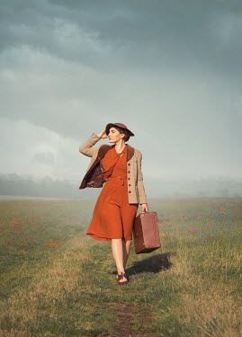 Joanna Czogala Young woman with beige coat and suitcase walking in field