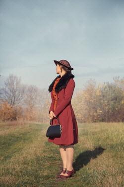 Joanna Czogala Young woman in red coat in field