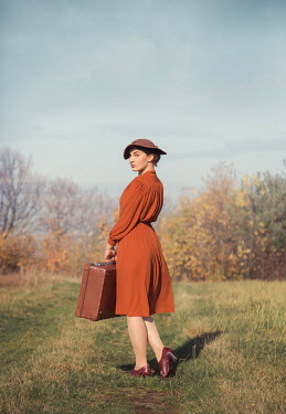 Joanna Czogala Young woman with orange dress and suitcase walking in field