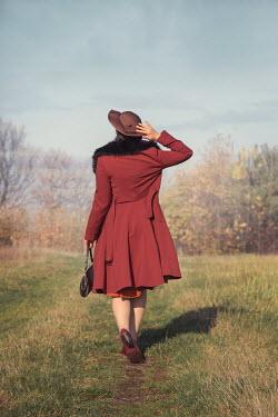 Joanna Czogala Young woman in red coat walking in field