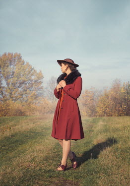 Joanna Czogala Young woman in red coat walking in field