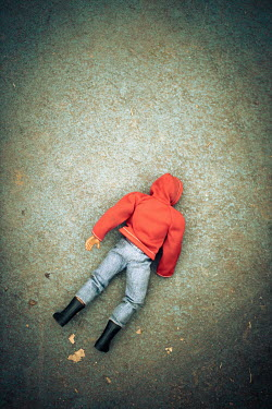 Paolo Martinez Action figure in red hoodie lying on concrete